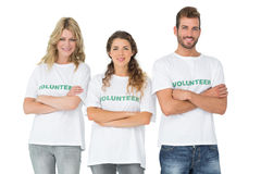 Portrait of three happy volunteers standing with hands crossed Royalty Free Stock Photo