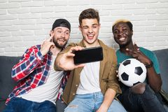 Portrait of three happy young men taking a selfie on phone while sitting at home with beer and snacks stock image