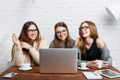 Portrait of three laughing girlfriends with laptop. Stock Photo