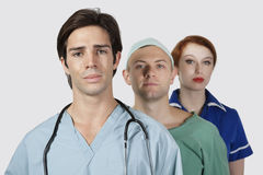 Portrait of three medical practitioners against gray background Royalty Free Stock Photography