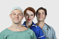 Portrait of three medical practitioners smiling together against gray background Stock Photos