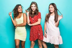 Portrait of Three mixed race best friends posing in studio, wearing summer style dresses against blue wall . Girls smiling and stock photography