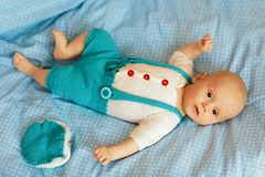 Portrait of a three months old baby boy on the bed on a blue blanket in nursery room. Flat lay.  royalty free stock images