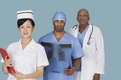 Portrait of three multi ethnic medical professionals over light blue background Royalty Free Stock Photos