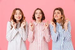 Portrait of three pleased young girls 20s wearing colorful strip stock photo