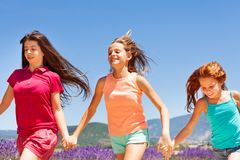 Three happy girls running together outdoors Royalty Free Stock Images