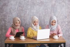 Three siblings wearing hijab are busy on their own gadget. Portrait of three siblings wearing hijab are busy on their own gadget with concrete wall background Royalty Free Stock Images