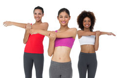Portrait of three sporty young women stretching hands Stock Photo
