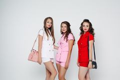 Fashionable ladies in trendy summer office suits with shorts and crossbags.