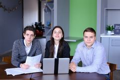 Portrait of three successful male and female students or colleag. Three educated employees of company, two guys and girl look with smile at camera and pose, are Royalty Free Stock Photography