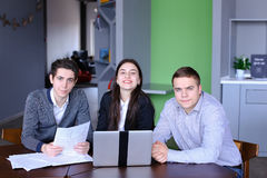 Portrait of three successful male and female students or colleag. Three educated employees of company, two guys and girl look with smile at camera and pose, are Royalty Free Stock Images