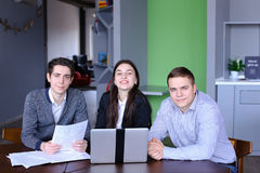 Portrait of three successful male and female students or colleag. Three educated employees of company, two guys and girl look with smile at camera and pose, are Royalty Free Stock Photo