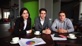 Portrait of three successful male and female students or colleagues who are looking at camera with smile, sitting in. Three educated employees of company, two stock video footage