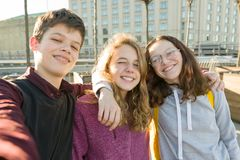 Portrait of three teen friends boy and two girls smiling and taking a selfie outdoors royalty free stock photography