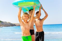 Happy boys with air mattress overhead on the beach. Portrait of three teenage boys, happy friends, standing on the beach with big inflatable mattress overhead royalty free stock photo