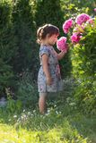 Portrait of a three year old girl playing in the garden. Stock Image