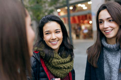 Portrait of three young beautiful women talking and laughing. Stock Image