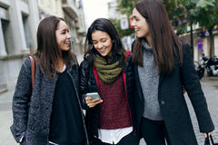 Portrait of three young beautiful women using mobile phone. Stock Photos