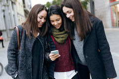Portrait of three young beautiful women using mobile phone. Royalty Free Stock Images