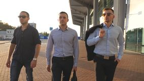 Portrait of three young businessmen walking in city near office. Business men commuting to work together. Confident guys. Being on his way to job. Colleagues stock video footage