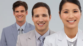 Portrait of three young businesspeople smiling. At the camera standing against a white background Royalty Free Stock Images