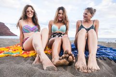 Unusual point of view with three young beautiful women taking sunbath and enjoying the vacation in a tropical sandy beach together. Portrait of three young royalty free stock photography