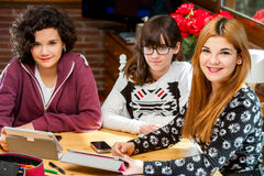 Portrait of three young female students at desk. Stock Photos