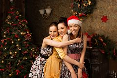 Portrait of  three young woman posing near decorated Christmas t Stock Photo