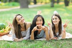 Portrait of three young women showing sign peace and heart. One Asian girl and two Caucasian having fun outdoors. Female friendship concept. Models smiling and Royalty Free Stock Photo