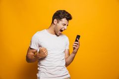 Portrait of a thrilled young man looking at mobile phone. Isolated over yellow background, celebrating royalty free stock image