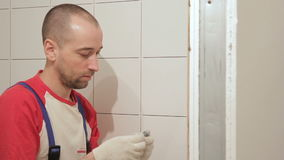 Portrait of a tiler who lays tile in the corner of the room. stock footage