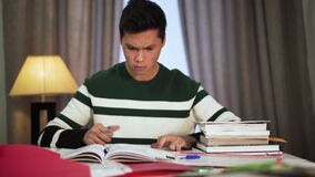 Portrait of tired Asian male college student sitting with books at home. Young handsome boy putting head on hand and