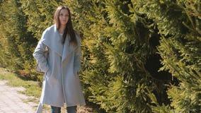 Portrait of tired beautiful brunette woman in coat walking in spring park. Portrait of tired beautiful brunette woman in coat walking in spring park stock footage
