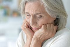 Portrait of tired beautiful senior woman posing at home stock photography