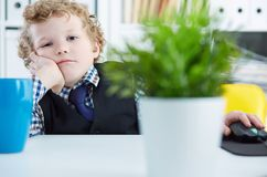 Portrait of tired business child wearing formal shirt and tie. Cute little boy covering his mouth with hands, imitating. Portrait of tired business child wearing Stock Photos