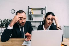 Portrait of tired business people looking at laptop screen at workplace. In office royalty free stock photos