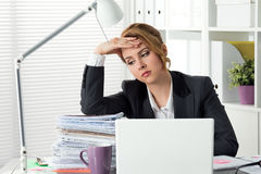 Portrait of tired businesswoman sitting at her office. Near huge heap of papers and holding her head. Woman don`t know what to do. Problems, stress at work Royalty Free Stock Images