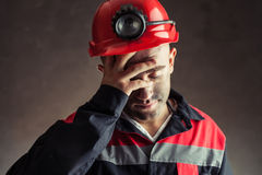 Portrait of tired coal miner. Holding hand his head against a dark background Stock Photography