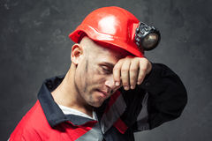 Portrait of tired coal miner. Wiping forehead his hand against a dark background Stock Photography
