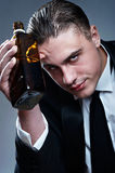 Portrait of tired drunk man with whiskey bottle Royalty Free Stock Images