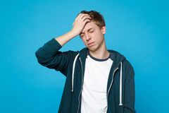 Portrait of tired exhausted young man in casual clothes keeping eyes closed, putting hand on head isolated on blue stock photos