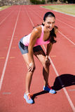 Portrait of tired female athlete standing on running track Stock Photos