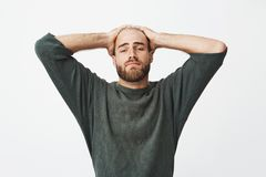 Portrait of tired handsome man holding hands on head, leaning back on chair to rest for a few minutes during hard day in Stock Images