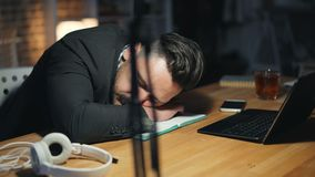 Portrait of tired handsome man sleeping on desk in dark office late at night