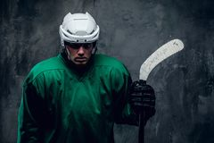 Portrait of tired hockey player in protective uniform. Portrait of tired hockey player in protective uniform in a shadow on grey background stock photography