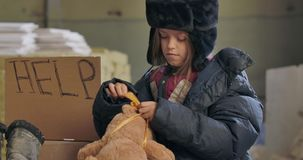 Portrait of a tired homeless child in dirty clothes trying to tie a bow on the teddy bear with frozen hands. Desperate stock footage
