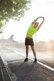 Portrait of tired jogger makes the warm-up to complete morning jog in urban setting Royalty Free Stock Photography