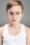 Portrait of tired little boy in glasses. On grey Royalty Free Stock Photo