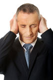 Portrait of tired man covering ears with hands Royalty Free Stock Photo
