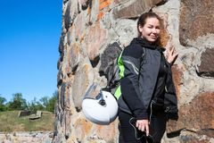 Portrait of tired motorcyclist woman resting near stone wall after tramp a fortress in apparel, with backpack and helmet attached. Portrait of tired motorcyclist stock image
